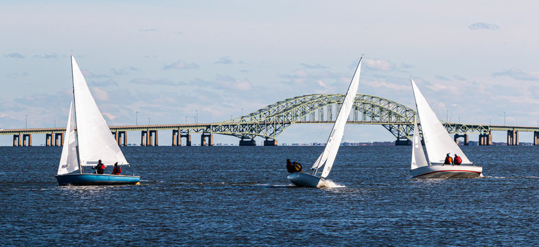 Three two person sailboats in front of the Great South Bay bridge on a windy December afternoon
