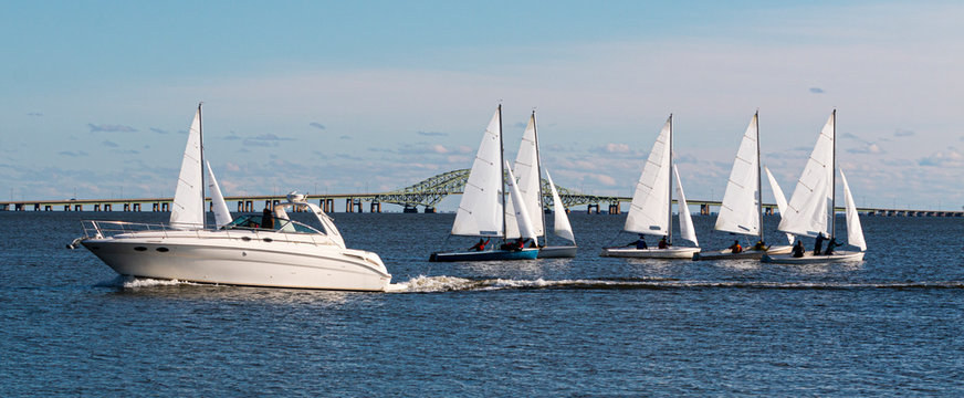 Two person sailboats in December regatta with large motorboat passing infront of them and bridge in background