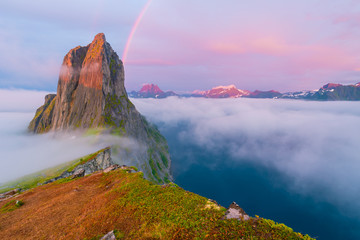 Tuinposter Purper Pink dawn with a rainbow above the clouds in Norway on the mountain Segla