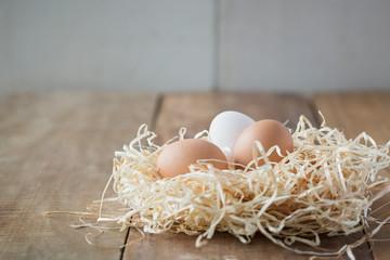 Brown and white eggs in raffia nest