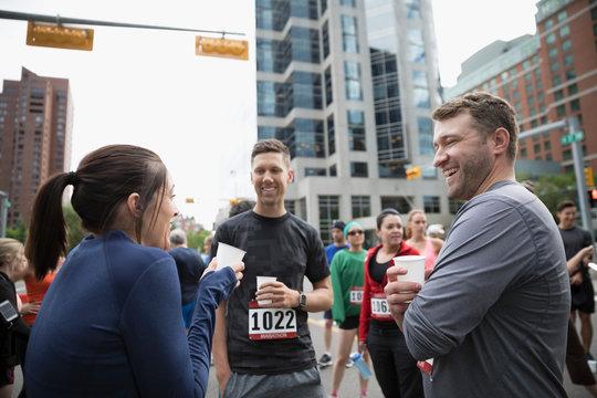 Marathon runners talking and drinking water on urban street