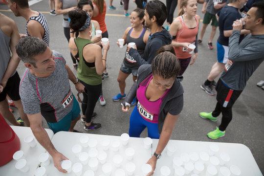 Marathon runners drinking water at water station