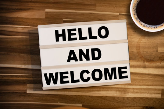 Lightbox or light box with message Hello and welcome on a wooden table