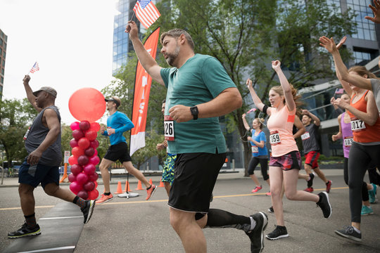 Marathon runners with American flags crossing finish line