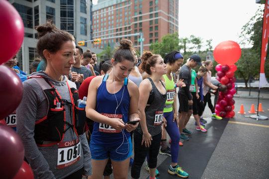 Marathon runners ready, waiting at starting line on urban street
