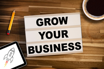 Lightbox or light box with business equipment and message Grow your business