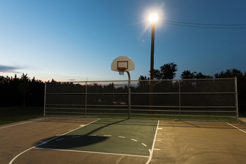 Basketball court lit by floodlight at night