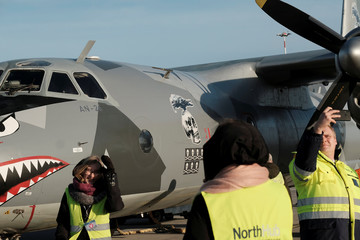 People takes pictures next to the Eleron Antonov AN-26B plane UR-CSK in Riga International Airport in Riga