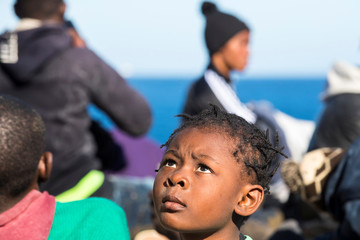 A child looks on as at least 27 migrants reached in a dinghy boat the beach of El Burrero in Gran Canaria