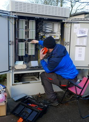Test work on an outdoor distribution box. Technician working outside on a telecommunication distribution cabinet.