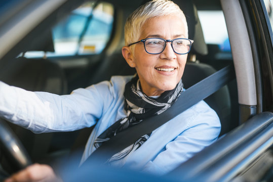 Happy and smiling senior woman in black car