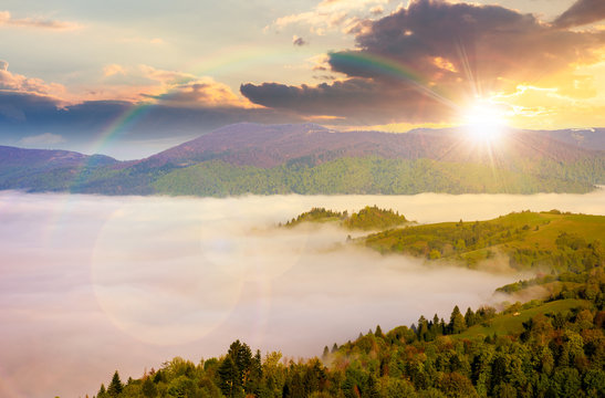 mountainous countryside at sunset. valley full of rising fog in evening light. green foliage on trees. wonderful nature scenery with rainbow in springtime