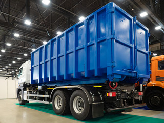 Demonstration trucks. Blue truck body. The body of the truck for garbage collection. Demonstration of equipment for housing and communal services. Metal container for garbage collection on wheels.