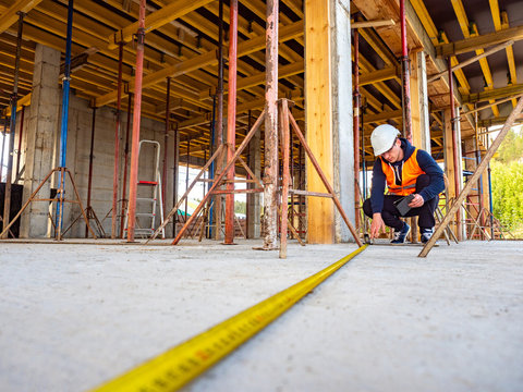 Construction of cottages. The foreman checks compliance of the performed works to the project of the house. Determination of the size of the premises. Measuring tape. Building frame.