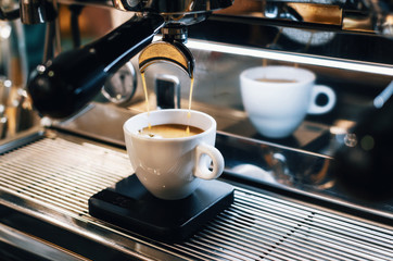 Professional espresso machine pouring fresh coffee into white ceramic cup with reflection on background