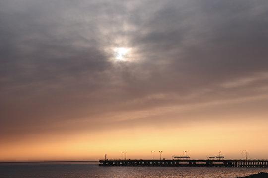 Sun behind clouds above sea horizon. Beautiful orange sky over skyline at sunset. Sunrays break through the heavens. Dais on water line. Silhouette of platform in distance.