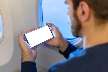 Mockup smartphone airplane. Young attractive european man holding blank screen smartphone in hands in airplane. Mock up for a game, mobile application, web site a horizontal oriental. Stock photo.