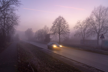 Tuinposter Purper car on foggy road at sunset