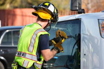 Emergency Responder Sawing Through Window on Mini Van