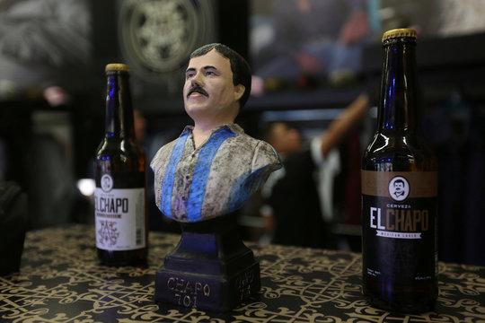 "Bust of Mexican kingpin Joaquin ""El Chapo"" Guzman stand between bottles of ""el Chapo"" beer, at the Expo Guadalajara"
