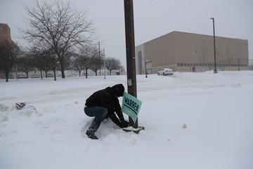 A man places a banner of Democratic 2020 U.S. presidential candidate and U.S. Senator Elizabeth Warren (D-MA) in Newton