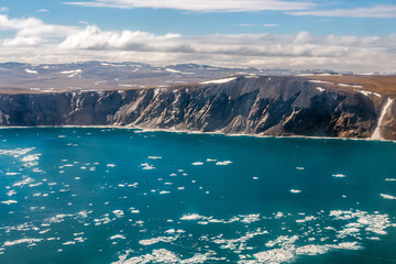 Summer aerial view of the coast of the Arctic Ocean. Top view of the sea, ice floes, steep coast and tundra. The amazing nature of the Arctic. Chukchi Sea, Chukotka, Polar Siberia, Far East of Russia.
