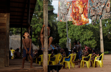Indigenous kids of Kayapo tribe play outside their house as people of various tribes attend a meeting during a four-day pow wow in Piaracu village near Sao Jose do Xingu, Mato Grosso state
