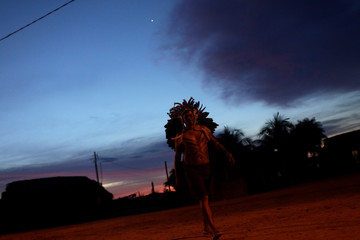 An indigenous man walks as the sun sets during a four-day pow wow in Piaracu village near Sao Jose do Xingu