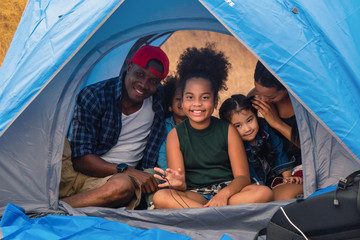 african american family, parent with kids, and asian adoped child having fun together in camping at natural park