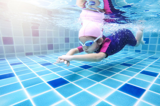 Underwater young little cute girl is swimming in the swimming pool with her swimming teacher. Seen under water while she is diving forward ahead of her. Swimming kid in the pool concept.