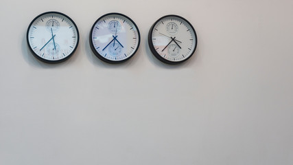 Three wall clocks showing time in different capitals of the world.