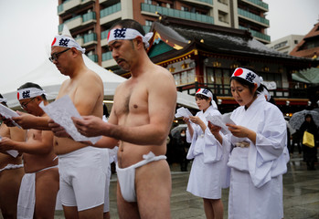 Participants hold a ritual ceremony before the annual cold water endurance ceremony, to purify their souls and wish for good fortune in the new year, at the Kanda Myojin shrine in Tokyo