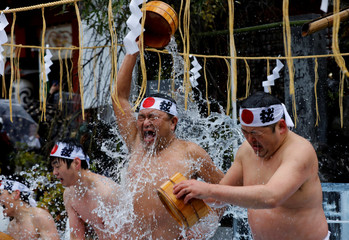 Men splash themselves with cold water during the annual cold water endurance ceremony, to purify their souls and wish for good fortune in the new year, at the Kanda Myojin shrine in Tokyo