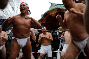 Men warm up before entering cold water during the annual cold water endurance ceremony, to purify their souls and wish for good fortune in the new year, at the Kanda Myojin shrine in Tokyo