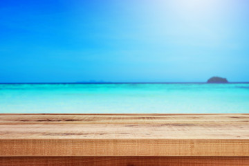 Blurred nature summer tropical beach background and wooden table.
