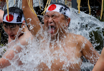 A man splashes himself with cold water during the annual cold water endurance ceremony, to purify his soul and wish for good fortune in the new year, at the Kanda Myojin shrine in Tokyo