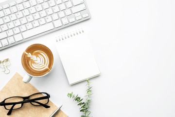 Wall Mural - White office desk table with small blank notebook, cup of latte coffee and office supplies. Top view with copy space, flat lay.