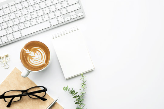 White office desk table with small blank notebook, cup of latte coffee and office supplies. Top view with copy space, flat lay.