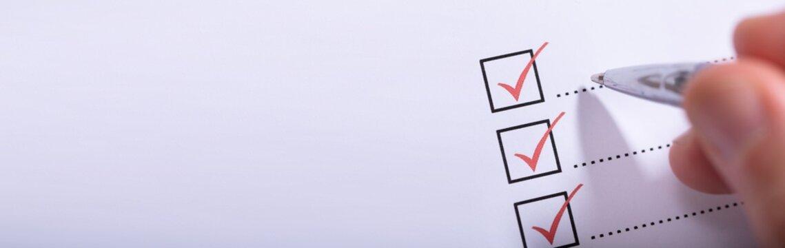 Person's Hand Marking On Checklist