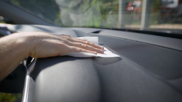 A man rubs a car with a napkin. Care and cleaning of the interior panels of the premium car is carried out. The interior of the car is made of quality materials.