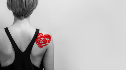 Decorative tattoo red heart on a shoulder, black and white. Valentines day party concept or skin spa treatment