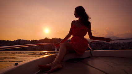romantic young woman is sitting on board of small pleasure boat in sunset time, leaning on handrails