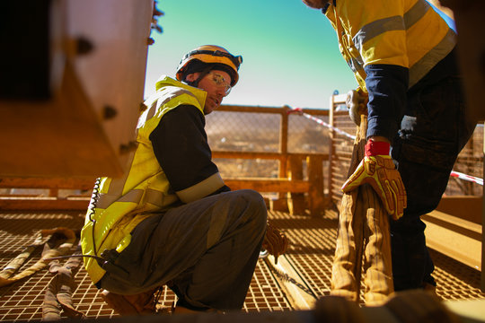 Defocused rigger wearing fall safety helmet clear glass friend hand wearing safety final safety check of three tone crane lifting sling inspection before commencing task construction site Australia