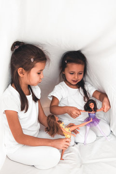 Little girls in bed play with dolls. Joy, family, fun