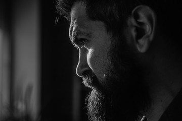 Handsome and confident. Outdoor portrait of young man with beard. Portrait of a bearded man with an intense look standing in a dark room against a black background. Papier Peint