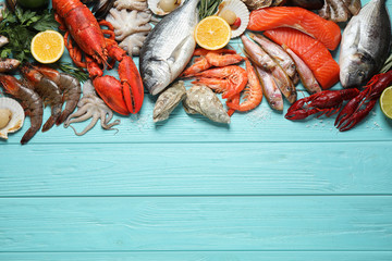 Fresh fish and different seafood on blue wooden table, flat lay. Space for text
