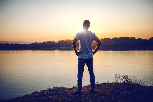 Rear view of handsome caucasian man standing with hands on hips on cliff and looking at river and beautiful sunset.