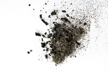 Randomly scattered pile of ash on a light background. Selective focus.