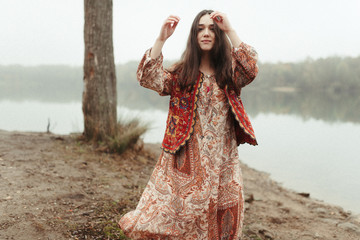 Young hippie girl in red outfit dancing by a lake Fototapete