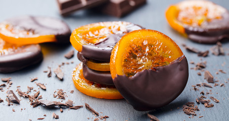 Candied orange slices in chocolate. Slate background. Close up. Fototapete
